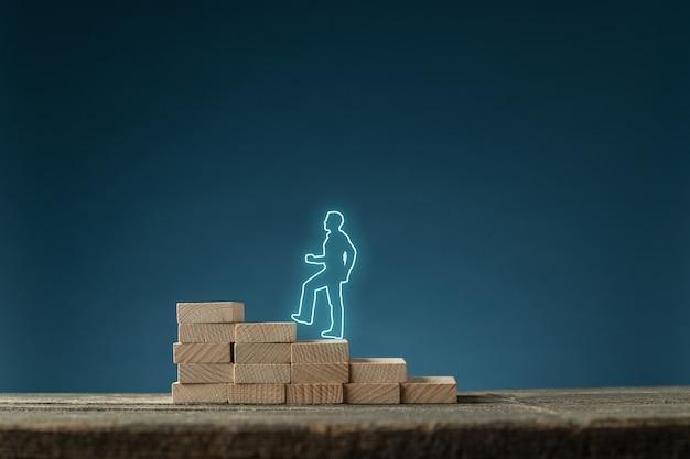 Gloeiende sihouette van zakenman die de trap oploopt, gemaakt van houten pinnen in een conceptueel beeld. met kopie ruimte over blauwe achtergrond.