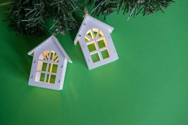 Gloeiende slinger van houten gezellige huizen op een groen nieuwjaarskerstmisconcept