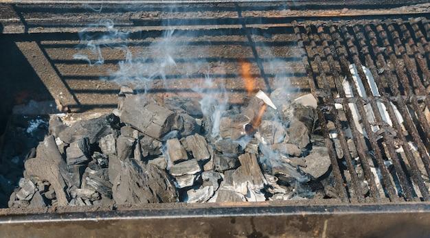 Gloeiende steenkolen in een rook van de barbecue steenkoolbrand