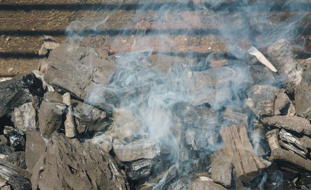 Gloeiende steenkolen in een rook van de de steenkoolbrand van de barbecuegrill