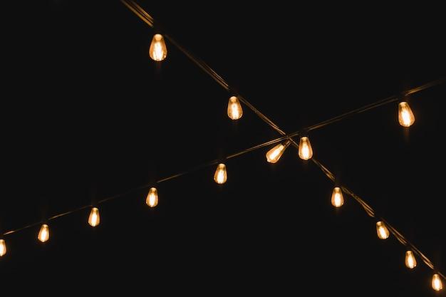 Gloeilamp decor in buitenfeest. decoratieve buitenlichtslingers 's nachts. gouden gloeiende garlandon in bruiloft