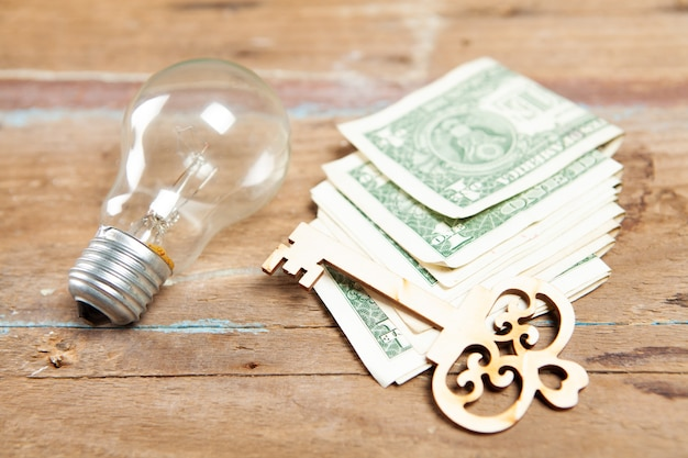 Gloeilamp, geld en sleutel op een houten tafel