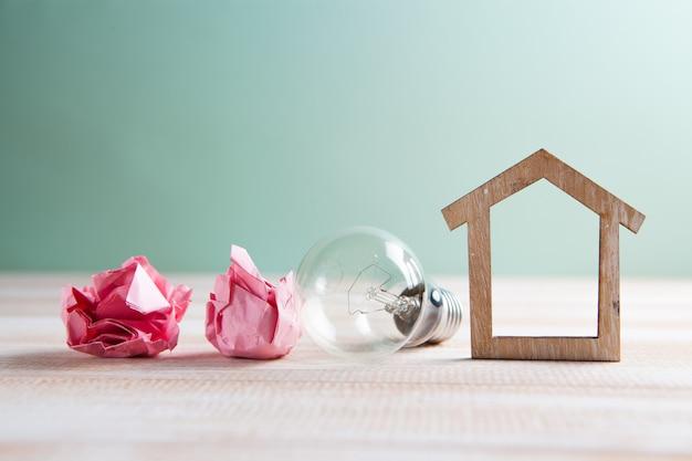 Gloeilamp, huis en proppen papier op tafel. ideeën voor thuisconcept