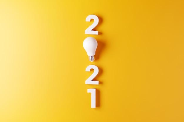Gloeilamp idee met nieuwe jaar gele achtergrond 2021.