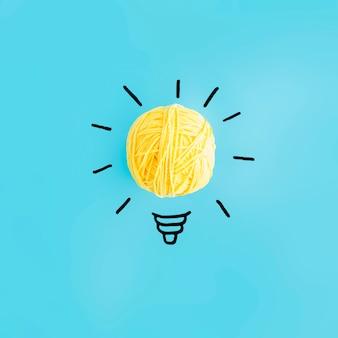 Gloeilamp met gele bal van garen op blauwe achtergrond wordt gemaakt die