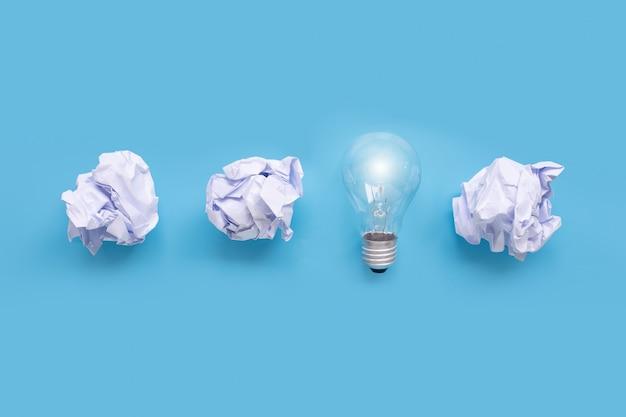 Gloeilamp met witte verfrommeld papier bal op blauwe achtergrond.