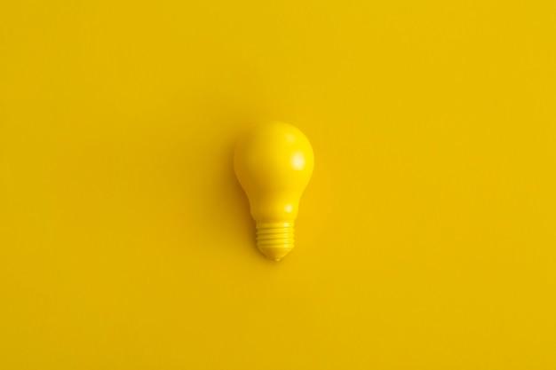 Gloeilamp op gele achtergrond. inspiratie en creatief idee concept. bovenaanzicht met kopie ruimte. platliggende compositie.