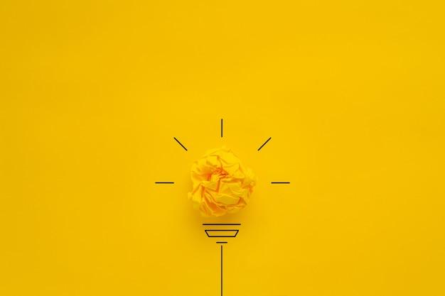 Gloeilamp over gele achtergrond in visie en idee conceptueel beeld