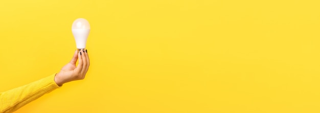 Gloeilamp ter beschikking over gele achtergrond