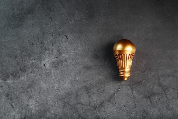 Gloeilamp van goud op zwarte steen concept van een winstgevend idee