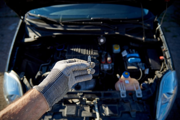 Gloeilamp voor de koplampen van een auto in mannenhand, auto met een open kap.
