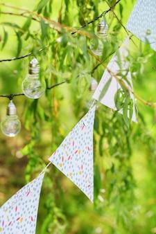 Gloeilampen en slingers hangen aan takken