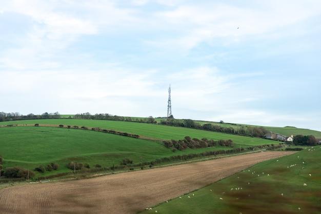Glooiende heuvel en een pyloon bij de nieuwe weg richting weymouth, dorset, uk