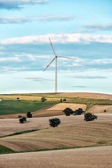 Glooiende heuvels met een enkele windturbine
