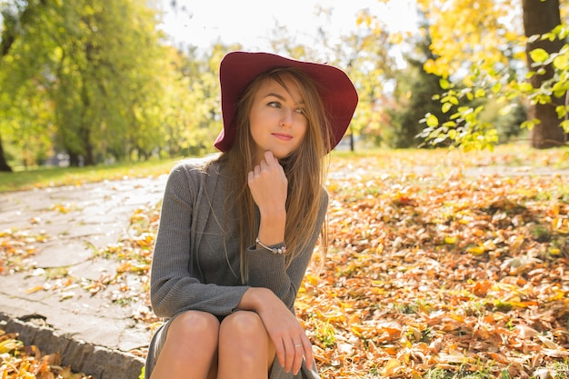 Glorieus blond model in rode hoed poserend in het bos, trendy gebreide jurk dragend