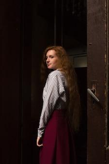 Glorieus jong roodharig model dat wit gestreept overhemd en rode rok draagt. vrouw poseren in een donkere kamer