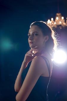Glorieuze brunette vrouw in zijden jurk poseren in een kamer met een kroonluchter en schaduwen