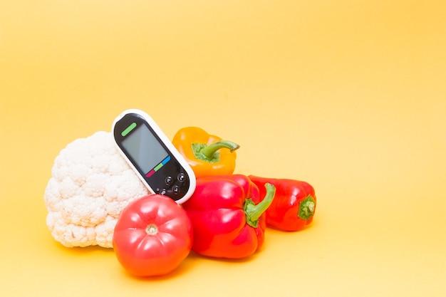 Glucosemeter en groenten op een gele achtergrondexemplaarruimte