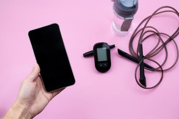 Glucosemeter lancet sportuitrusting en water met mobiele telefoon in de hand mock up diabetes preventie en behandeling concept afbeelding voor mobiele app