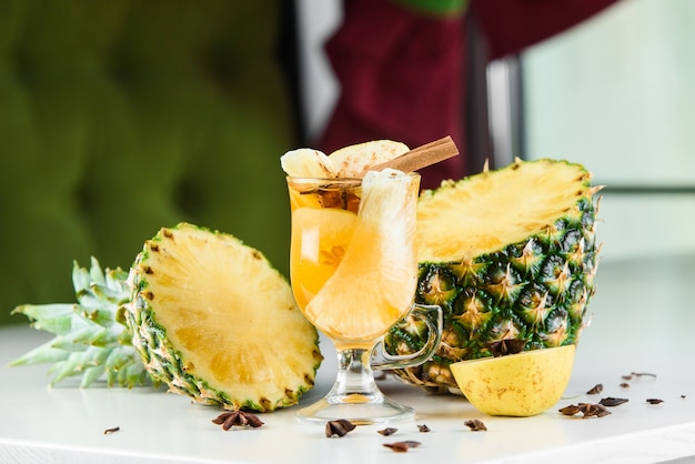 Glühwein, grog en punch warme alcoholische dranken op tafel met seizoensdecoratie: ananas, kaneel, appel, sinaasappel, steranijs. seizoensgebonden gekruide drank.