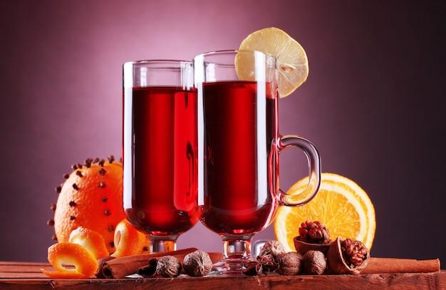 Glühwein in de glazen, kruiden en sinaasappel op houten tafel op paarse achtergrond