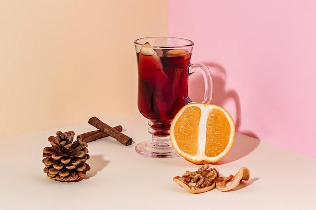 Glühwein in glas met kaneelstokje, kerstsnoepjes op de glazen tafel en fruit en gember op de achtergrond. winterconcept