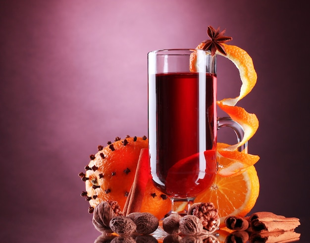 Glühwein in het glas, kruiden en sinaasappel op paarse achtergrond