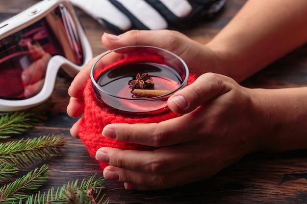 Glühwein in vrouw handen gezellige huis concept ingrediënten winter sport bril ski handschoenen