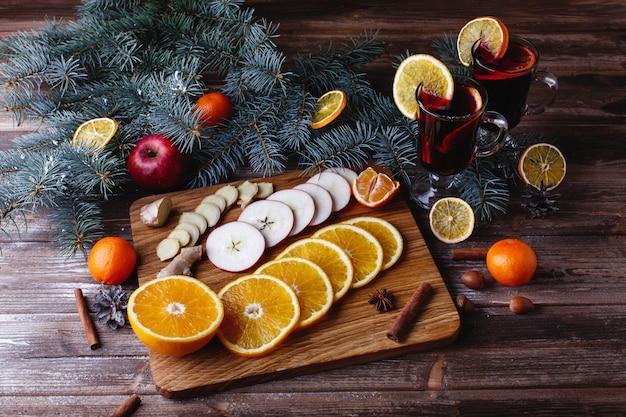 Glühwein koken. sinaasappelen, appels en soorten liggen op houten tafel