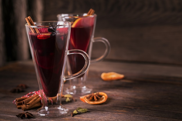 Glühwein met fruit, pijpjes kaneel en anijs op donkere houten achtergrond. winterverwarmend drankje met receptingrediënten.