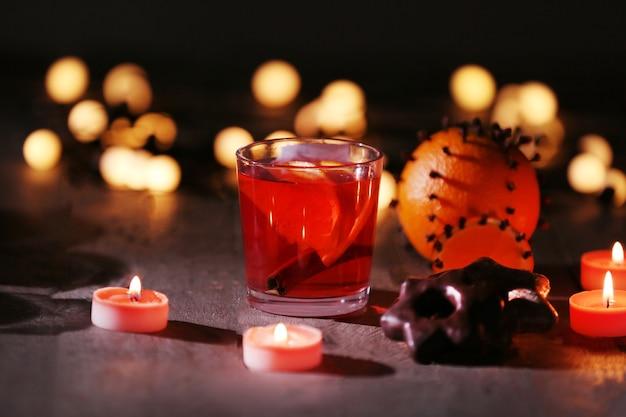 Glühwein met kruiden en kerstversiering op donkere houten ondergrond