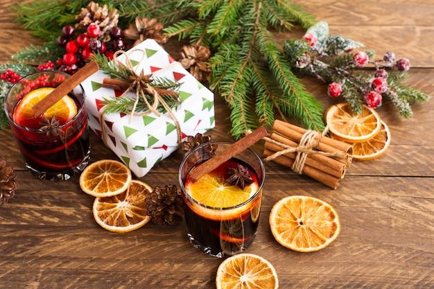 Glühwein met kruiden. kerstdecoratie met gedroogde stukjes sinaasappel. kaneelstokjes en kerstcadeautjes op houten achtergrond