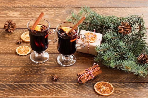 Glühwein met kruiden. kerstdecoratie met gedroogde stukjes sinaasappel. kaneelstokjes en kerstcadeautjes op houten ondergrond.