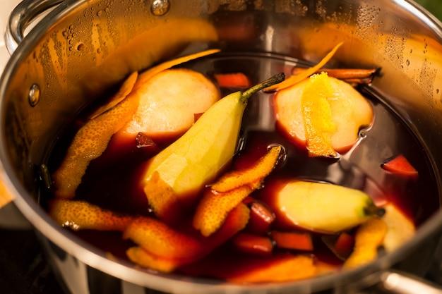 Glühwein met peren die in het koken van pot voorbereidingen treffen