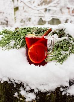 Glühwein op straat in de sneeuw met een tak van dennen