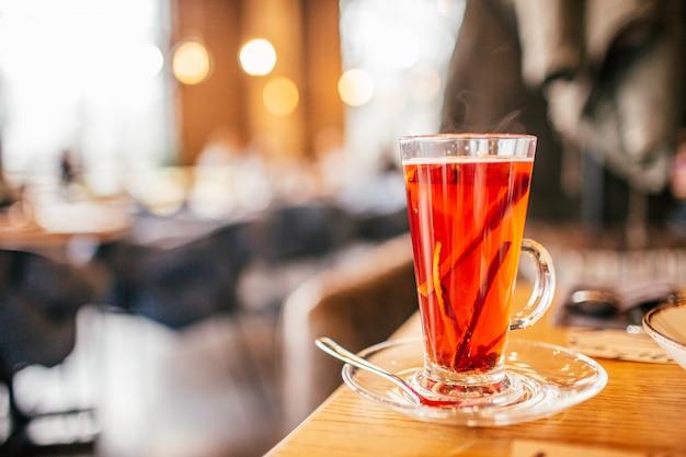 Glühwein rode wijn met specerijen en sinaasappelen op een rustieke houten tafel in restaurant
