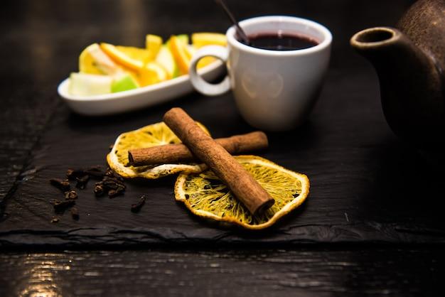Glühwein, sangria, glühwein in een witte kop op een donkere tafel, toog met fruit, thee en kruiden. pijpjes kaneel en sinaasappel