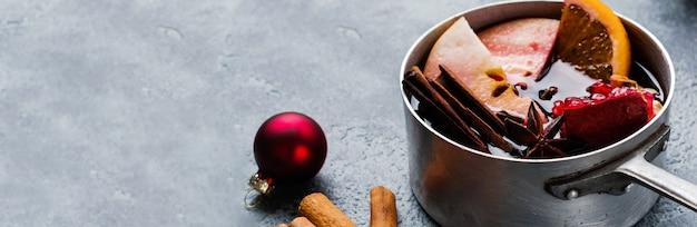 Glühwein warme drank met citrus, appel, granaatappel en kruiden in aluminium braadpan met vintage kerstboom speelgoed en fir branch op betonnen achtergrond. selectieve focus.