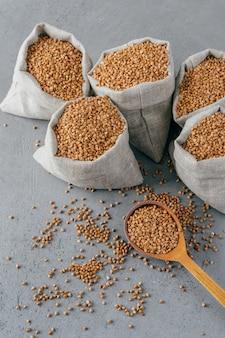 Glutenvrij product. verticaal schot van droog bruin boekweit voor vegetariërs. zakken met granen. houten lepel dichtbij. heathy eten concept