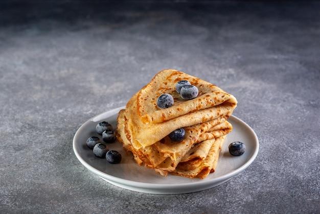 Glutenvrije pannenkoeken geserveerd met verse bosbessen op donkergrijze tafel