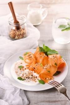Glutenvrije vegetarische salade met wortel en yoghurt gekruid met geplette noten en kruiden, muntafgietsels
