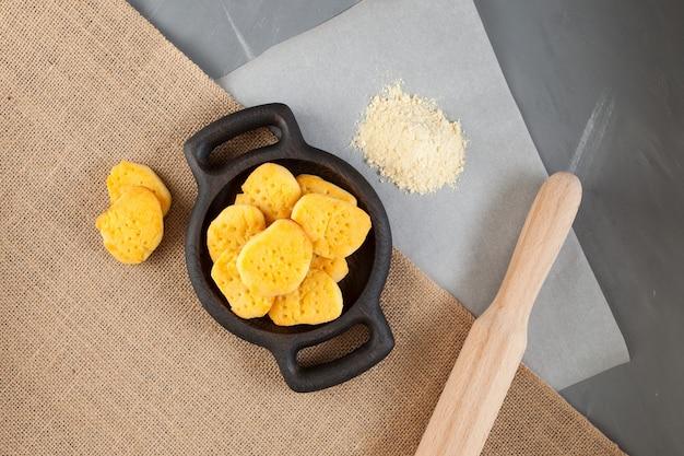Glutenvrije zelfgemaakte koekjes. meel op bakpapier en deegroller liggen op tafel.