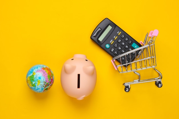 Gobal supermarkt. spaarvarken en winkelkarretje, bol, rekenmachine op geel