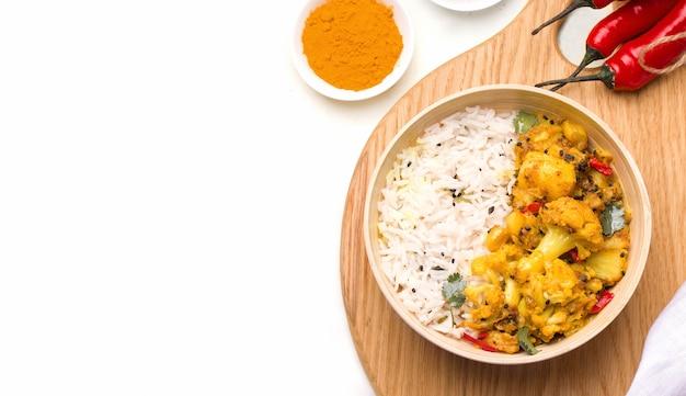 Gobi aloo indiase vegetarische schotel van groenten en aardappelen in een kom op een houten bord op wit