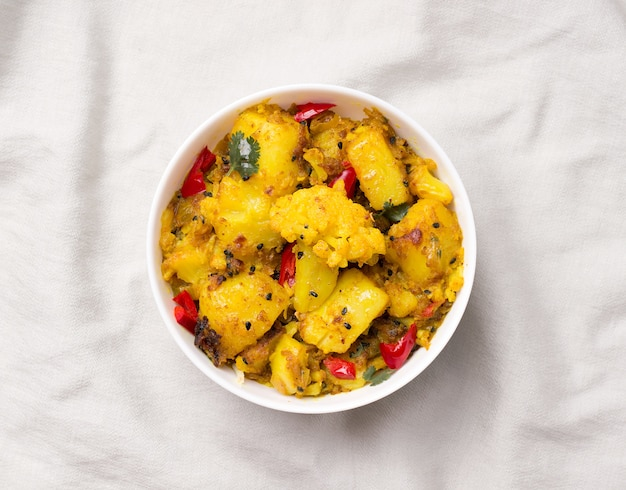Gobi aloo traditioneel indiaas gerecht van bloemkool en aardappelen op een grijze linnen stof