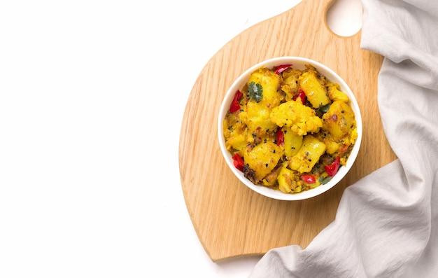 Gobi aloo traditionele indiase vegetarische schotel van aardappelen en bloemkool in een plaat op wit