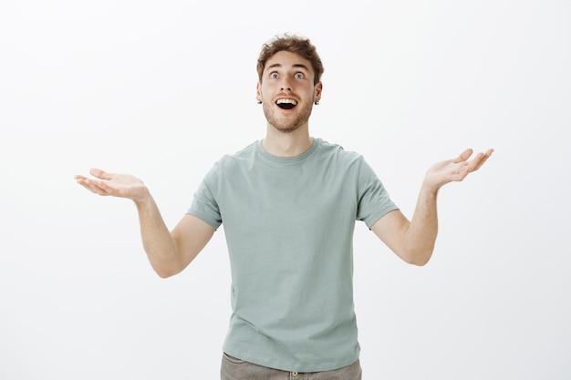God bedankt, eindelijk goed nieuws. portret van opgelucht en tevreden grappige europese man met varkenshaar in oorbellen, gespreide handpalmen opheffen en met brede glimlach opzoeken