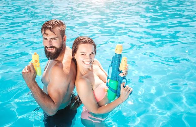 Goddelijk uitziende man en vrouw staan in het zwembad en kijken. ze poseren en glimlachen. mensen houden waterpistool in handen. ze zijn klaar om te schieten.