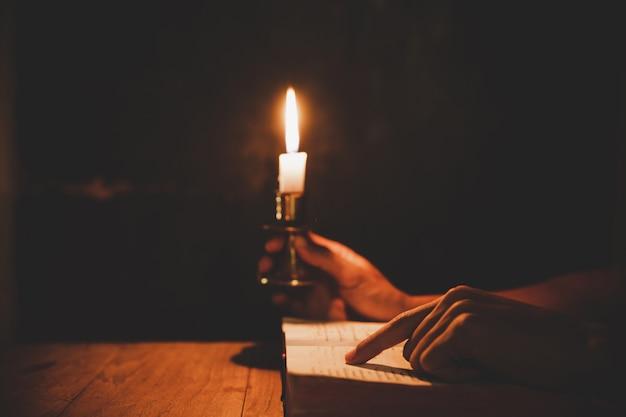 Godsdienstige mens die aangestoken kaarsen houden en de heilige bijbel lezen en in de kerk bidden