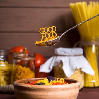 Goed eten is bekleed met pasta op een lepel in de buurt van een bord met kant en klare pasta